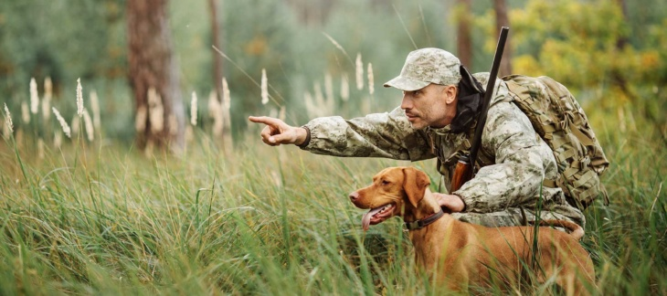 Man in camouflage pointing with hunting dog and squatting in tall grass
