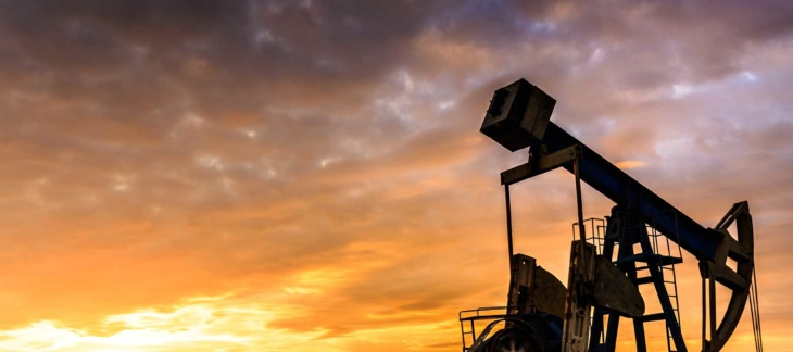 Profile of oil well at sunset