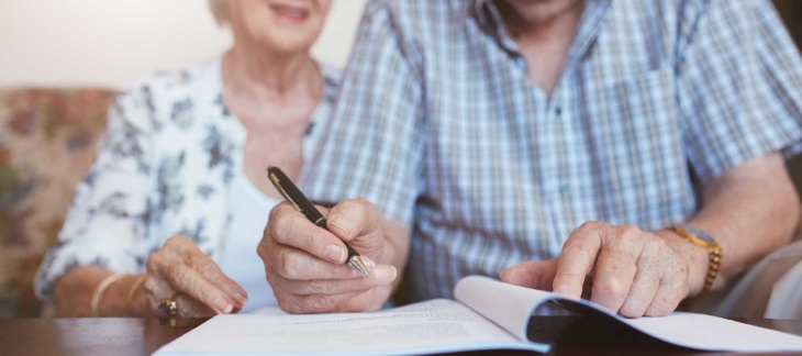 Older couple going over documents with pen in hand
